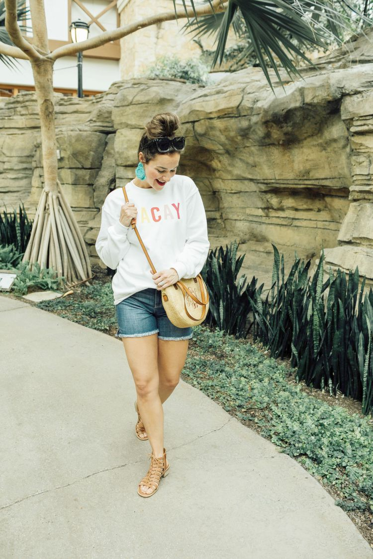 A Complete Dallas Travel Guide featured by top US travel blog, My Life Well Loved: image of a woman in Dallas wearing a Pink Lilly sweatshirt, Liverpool denim shorts, Marleylilly crossbody bag , Accessory Concierge statement earrings, zeroUV square sunglasses and Comfortiva sandals